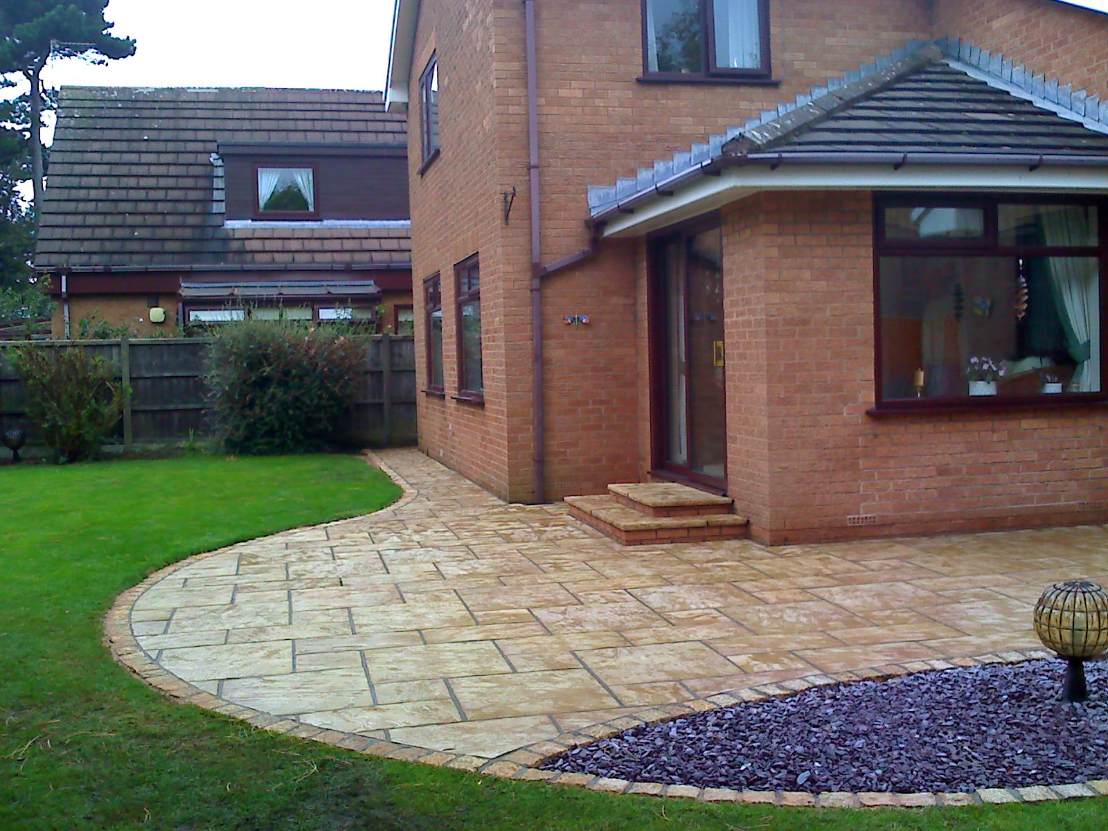 A large patio in an unique curved design using Marshalls Heritage with active shield in Yorkstone. We have used gold granite setts & Muddy Boots